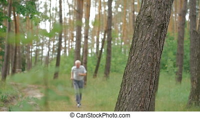 Old man running outdoors in a coniferous forest nature. Slow motion