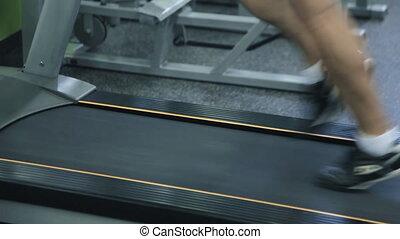 Old man runs on a treadmill