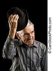 Old man saluting with hat, isolated on black