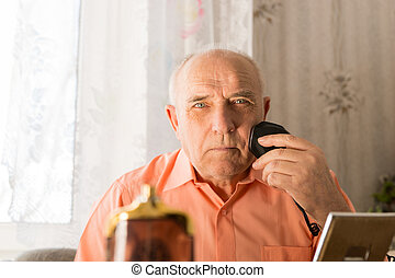 Old Man Shaving Hair on Face with Electric Razor