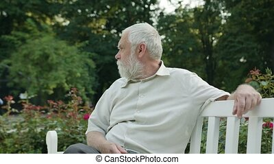 Old Man Sitting on a White Bench in the Park