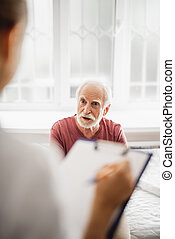 Old man sitting on bed and talking with doctor