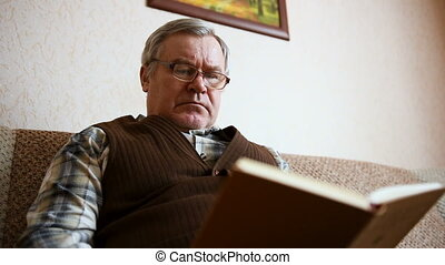 Old man sitting on the couch at home reading a book