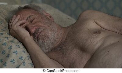 Old man sleeping at home - Old poor man sleeping on a bed at...