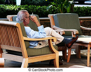 Old Man Smoking In A Chair