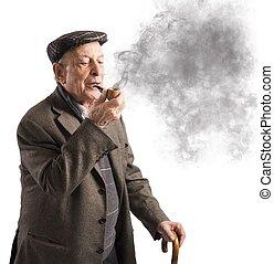 Old man smoking pipe - Old man reflecting while smoking his...