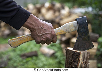 Old man splitting logs with ax