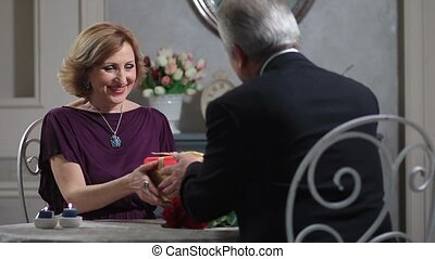 Old man surprising mature lady with present