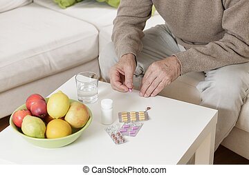 Old man taking medicines - Close up of sitting on sofa old...