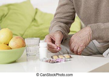 Old man taking pills - Ailing old man taking pills with...