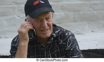 old man talking on a mobile phone