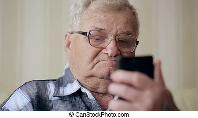 Old man text messaging through mobile phone on sofa.