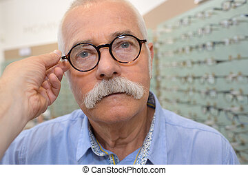 old man trying a pair of eyeglasses