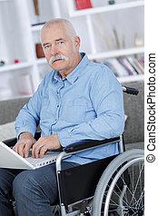 old man using a laptop