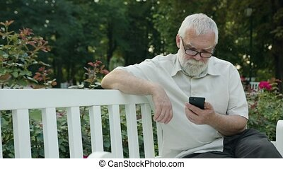 Old Man Using a Phone Outdoors