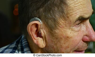 old man using hearing aids.