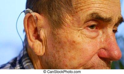 old man using hearing aids.