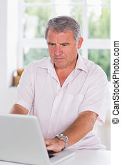Old man using laptop seriously in kitchen