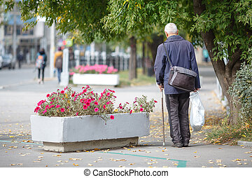 Old man walking with his hands on a wooden walking stick, natural
