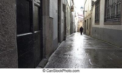 Old man walks in small alley in Santiago de Compostela,...