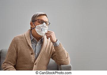 Old man wearing facemask during coronavirus and flu outbreak...