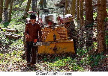 old man with a chainsaw in the forest