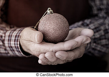 old man with a christmas ball in his hands