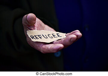 old man with a paper with the word refugee