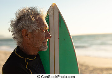 Old man with a surfboard at the beach
