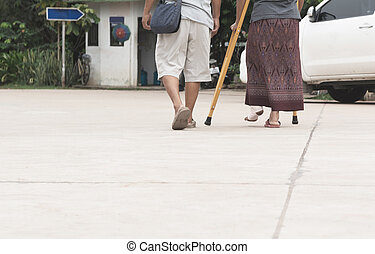 Old man with broken leg old woman walk together on street.