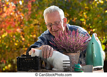 Old man with cat doing gardening work