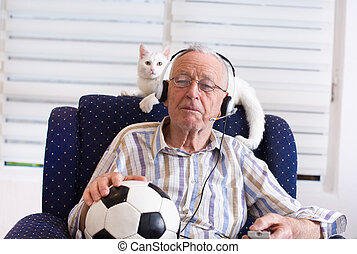 Old man with cat watching football match on tv