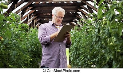 old man with clipboard in greenhouse on farm