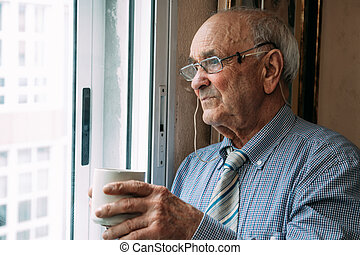 old man with cup of coffee at home window