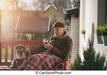 Old man with dog on bench smoking pipe