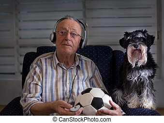 Old man with dog watching football match on tv