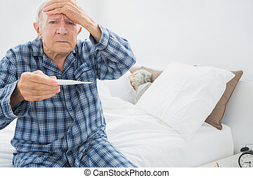 Old man with fever sitting on the bed