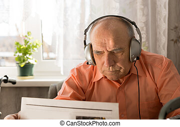 Old Man with Headset Reading Newspaper