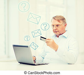 old man with laptop and credit card at home