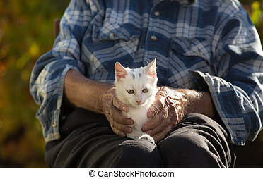 Old man with little cat in lap