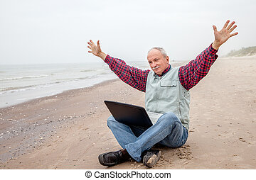 Old man with notebook on beach - Happy old man sitting on...
