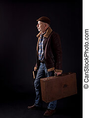 Old man with suitcase and book waiting