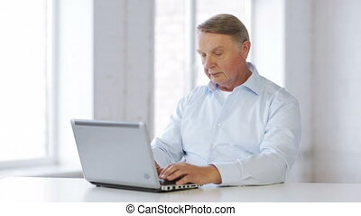 old man working with laptop at home