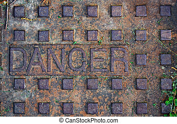 Old manhole with word danger