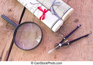 Old maps with drawing compass and magnifier on wooden desk