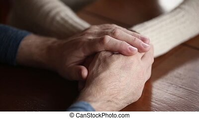 Old mature couple holding hands giving support and care concept