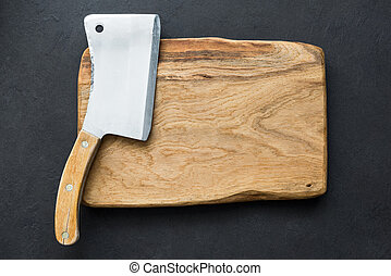 Old meat cleaver and chopping board, table top view