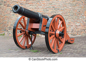Old medieval artillery canon before a brick wall
