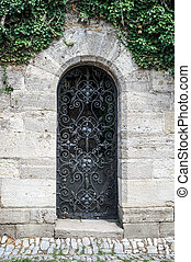Old medieval black metal door with cerved bar and light stone wall.