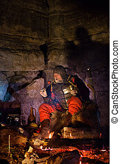Old medieval King in armor with dish is sitting on furs near the camp fire and having a lunch